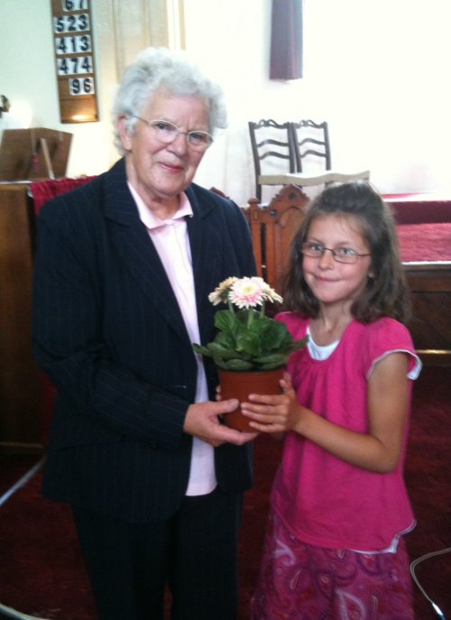 Chloe presents a pot of flowers to Esme