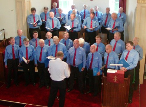 image of choir on dais, all in blue shirts, Bob Jones conducting