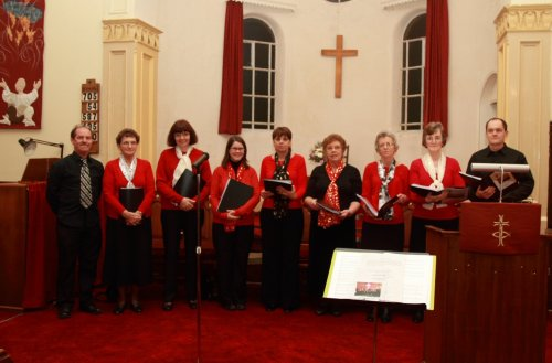 the praise group dressed in red and black in front of the cream coloured apse