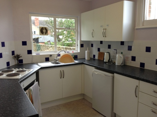 View of kitchen showing fittings with cooker, sink, fridge and kettles